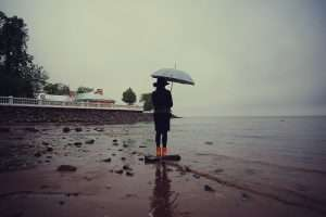 woman with an umbrella by the sea wind rain