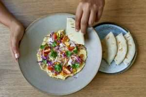 Overhead shot of tasty fine vegetarian plant-based international cuisine on artisanal ceramic plate including naan bread, tomatoes and herbs for mindful eating and a nutritious plant based diet.