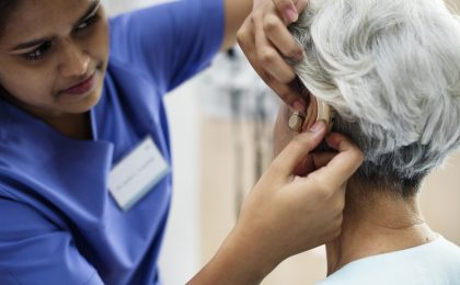 senior with hearing aid fitting